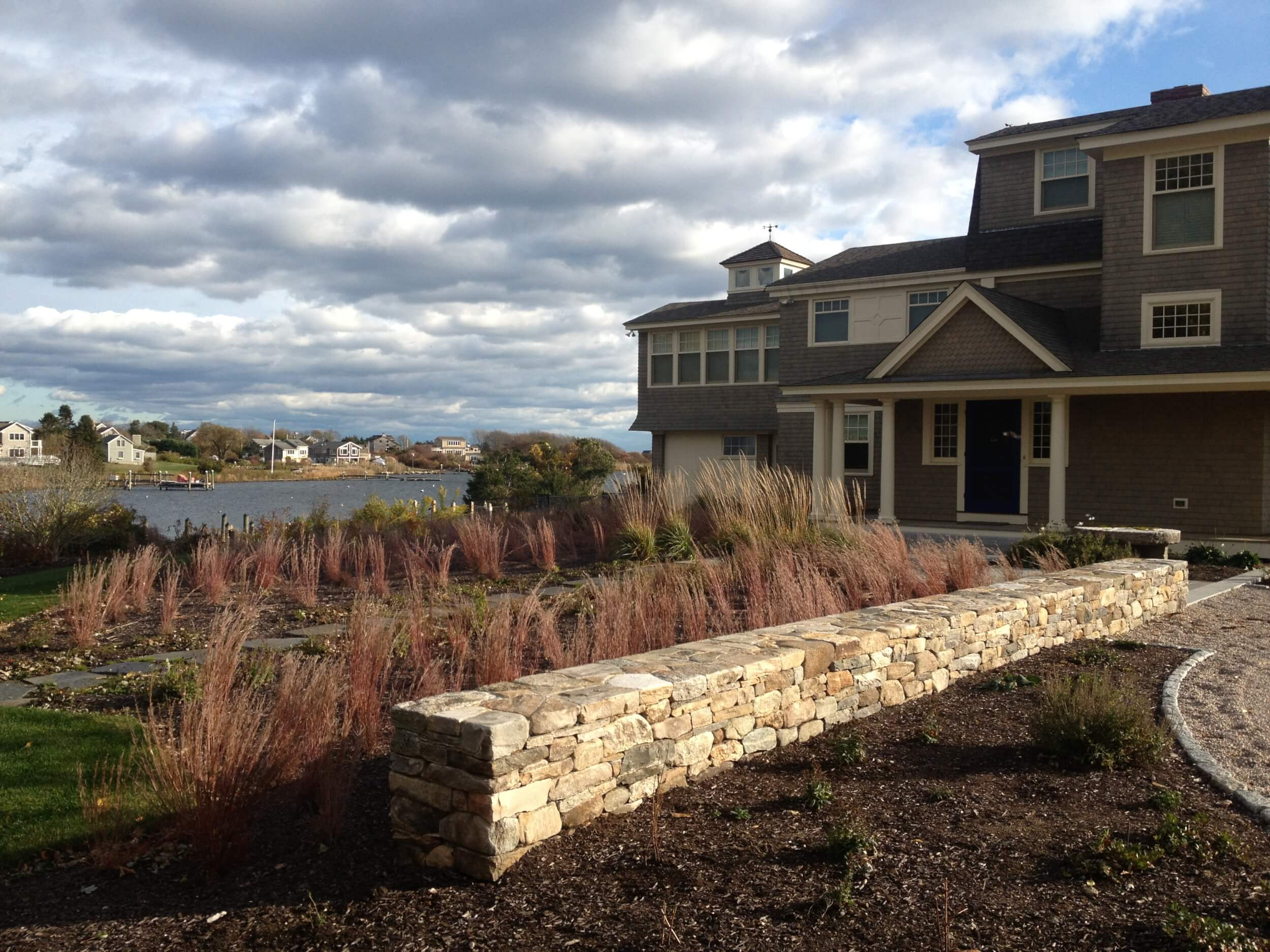 Meadow of native little bluestem grass softens coastal home while pulling feeling of water into the site from cove beyond.