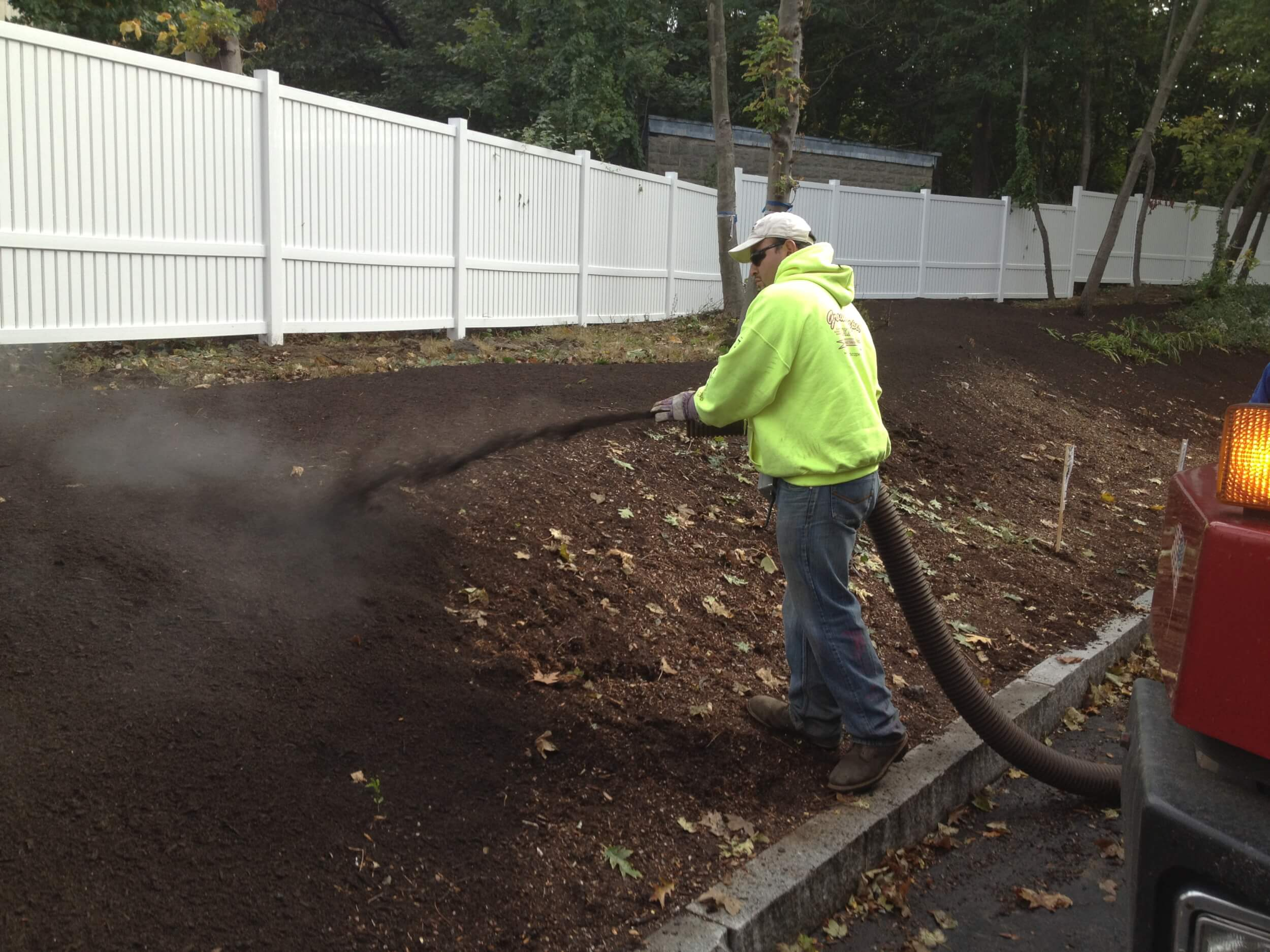 Replenishing depleted soils and stabilizing slopes with compost-mulch in preparation for planting at the JCHE campus in Boston.